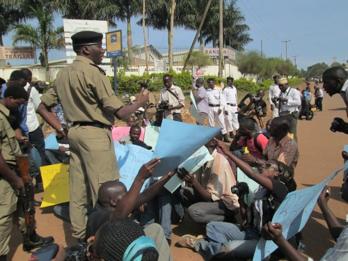 Assistant IGP Andrew Kaweesi argues with journalists trying to have a sit-in.