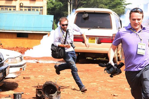 Two foreign correspondents dash away from a tear gas canister.